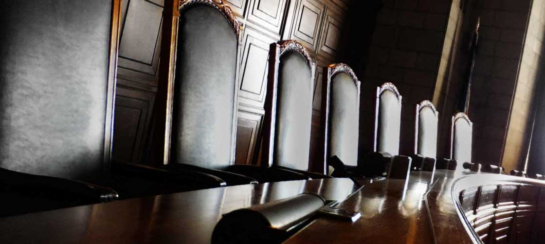 The beautiful leather chairs of the Nebraska Supreme Court are complimented by the fine wood work on the walls behind.